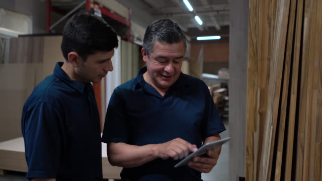 men working at a wood warehouse preparing an order using a tablet while talking and smiling - repairing stock videos & royalty-free footage