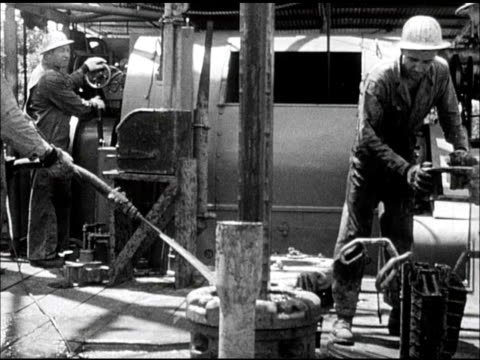 DRILLING Men working at base of derrick man holding water hose over drill driller raising drill up out of hole Teamwork dangerous work precision