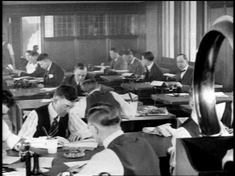 vidéos et rushes de b/w 1919 men working at desks in newspaper editorial office / newsreel - journalist