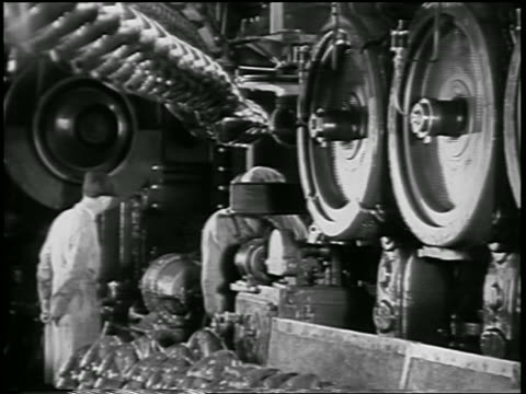 vidéos et rushes de b/w 1932 men working by large spinning wheels in ford car factory / industrial - ford