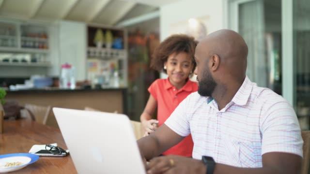 vídeos y material grabado en eventos de stock de hombres trabajando desde casa y hablando con su hija - intergénero