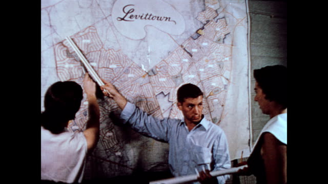 / Men working in architect's office / building plans everywhere / men and women consult map of Levittown community on wall / CU house drawing...