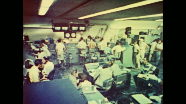 men working in crowded ground control offices prepare to fire an atlas missile - guerra fredda video stock e b–roll