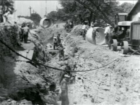 b/w 1934 men working in ditch in wpa sewage construction project / documentary - 雇用促進局点の映像素材/bロール