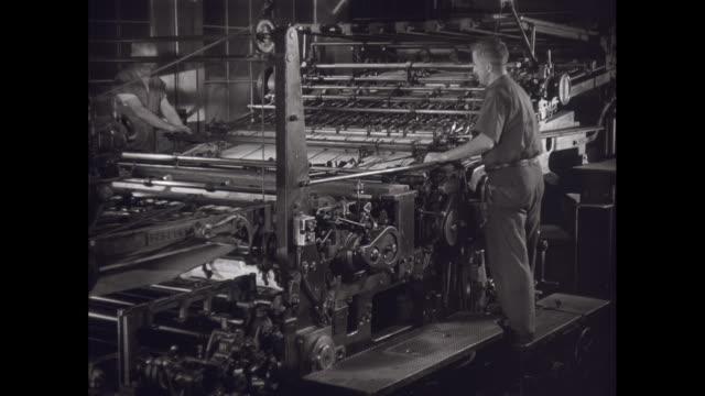 ms men working in printing press / united states - 印刷機点の映像素材/bロール