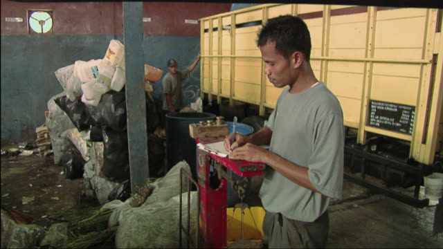 ms men working in recycling centre / bali, indonesia - リサイクル工場点の映像素材/bロール