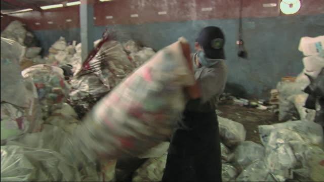 ws men working in recycling centre / bali, indonesia - ゴミ袋点の映像素材/bロール