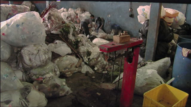 ws men working in recycling centre, heap of plastic bags in foreground / bali, indonesia - リサイクル工場点の映像素材/bロール