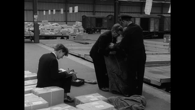 vidéos et rushes de men working in warehouse - paquet