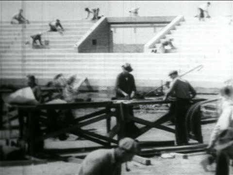 b/w 1934 men working in wpa stadium construction project / documentary - new deal video stock e b–roll