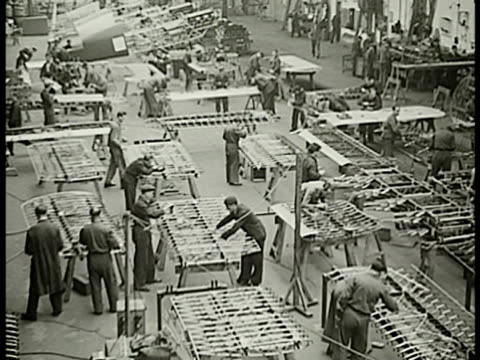 Men working on airplane frames wings MS Worker screwing working w/ frame workers sanding BG MS Men around metal frame of airplane one testing lever...