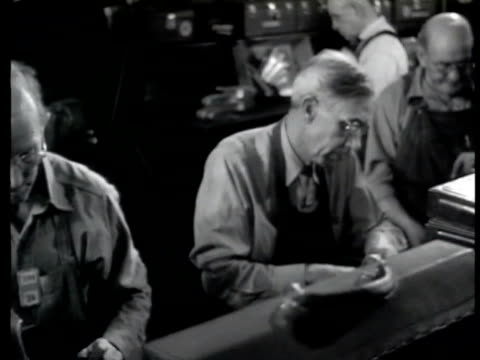 Men working on assembly line DOLLY PAST Middleaged men working on small parts grinding filing Sailor inspecting rivets signing paperwork Young adult...
