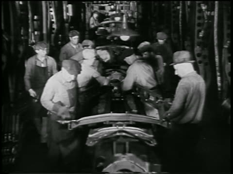 b/w 1932 men working on assembly line in ford car factory / industrial - 1932 stock-videos und b-roll-filmmaterial