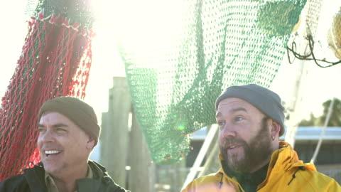 vidéos et rushes de hommes qui travaillaient sur le bateau de pêche commerciale converser - pont