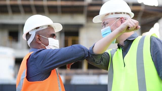 vidéos et rushes de hommes travaillant sur la construction, nouveau salutation utilisant le masque de protection faciale de coronavirus - règle de savoir vivre