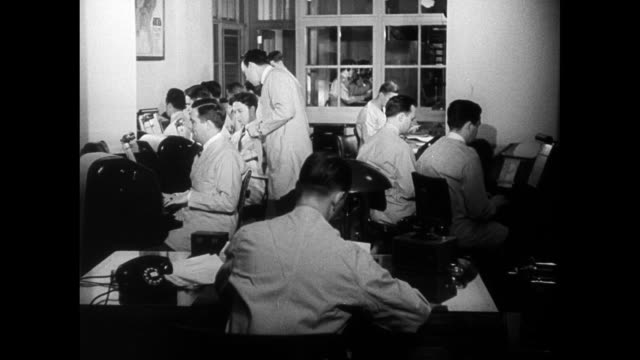 men working on fbi teletype machines. typing '...subject identified as foreign agent..not registered...' - fbi video stock e b–roll