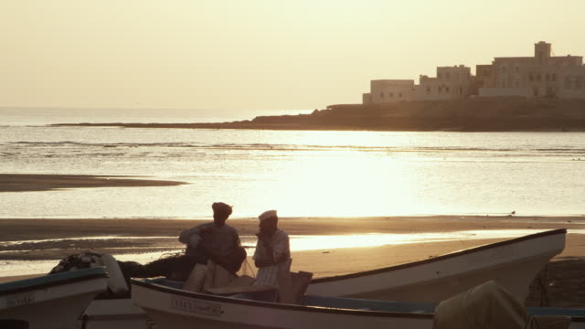 WS Men working on fishing boat with village and sunrise in background / Sur, Oman