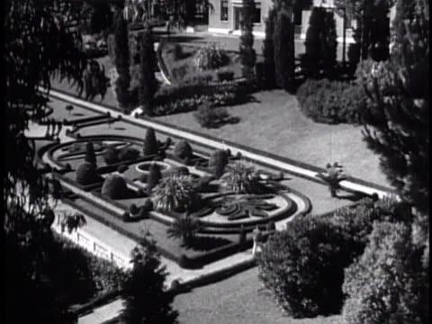 vídeos y material grabado en eventos de stock de men working on formal garden lawn next to planted design, parterre. formal garden w/ ornate design. two gardeners walking on garden sidewalk, care... - formal garden