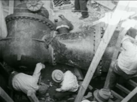 overhead men working on large pipes in wpa construction project / documentary - 雇用促進局点の映像素材/bロール
