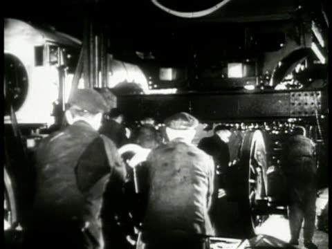 men working on locomotives on factory floor men pushing railroad train wheels men adjusting piston drive w/ huge wrench ls locomotive moving down... - piston stock videos & royalty-free footage