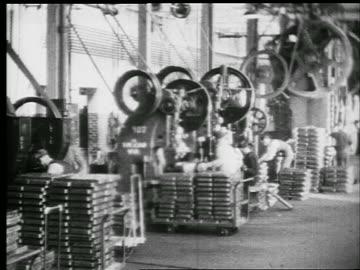 b/w 1929 pan men working on machinery with giant pulleys (steel punch presses) in factory / phil. - 1920 1929 bildbanksvideor och videomaterial från bakom kulisserna
