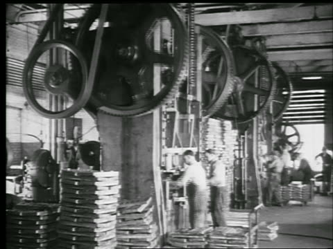 vídeos de stock, filmes e b-roll de b/w 1929 men working on machines with giant pulleys (steel punch presses) in factory / philadelphia - 1920 1929