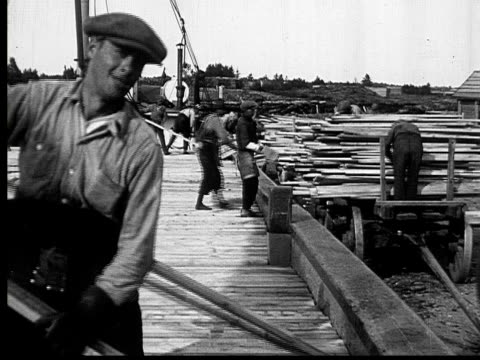 1927 B/W MONTAGE MS PAN HA Men working outside lumberyard unloading wooden planks from carts onto freight ships and wagons, Ontario, Canada