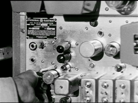 men working radio communications room. male hand adjusting knob on general electric radio plate, checking transmission. 'colonel' walking through... - pianificazione di emergenza video stock e b–roll