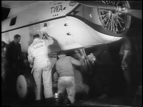 "men working underneath ""winnie mae"" prop airplane in hangar / newsreel - 1935 stock videos & royalty-free footage"
