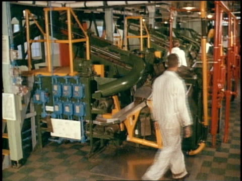 1967 MONTAGE men working with mass production ammunition, bullet machine. Bullets moving on conveyor belts. Stacked boxes of ammunition, boxes stamped U.S. Army /