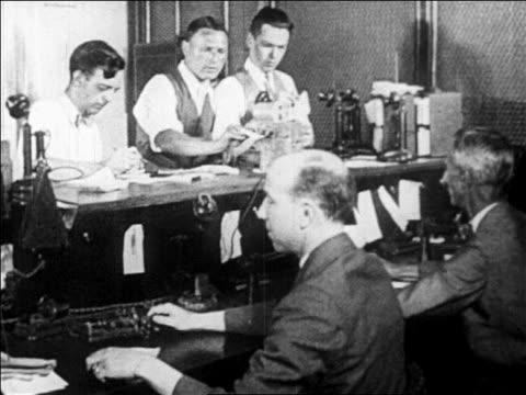 B/W 1929 men working with telephones in stocks and bonds office / newsreel