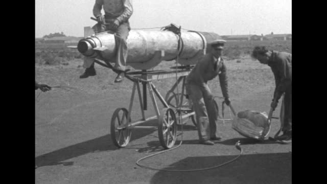 men wrangle a huge parachute / sailors at a torpedo mounted on wheels with one banging on it with a mallet / vs the men carry the folded parachute... - bundle stock videos & royalty-free footage