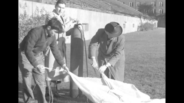 vídeos de stock, filmes e b-roll de vs men wrapping large balloon with fabric and filling one from tank of hydrogen / men carrying several balloons from building onto field / scientists... - hidrogênio