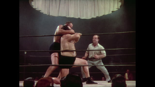 1937 Men wrestle on stage with enthusiastic referee, surrounded by audience at Madison Square Garden