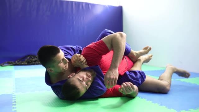 stockvideo's en b-roll-footage met mannen worstelen op de vloer in gym - worstelen