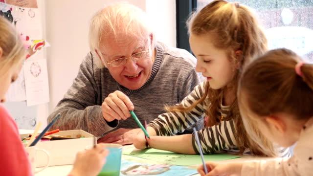 meningitis survivor malerei auf dem esstisch mit opa! - kunst und kunsthandwerk stock-videos und b-roll-filmmaterial