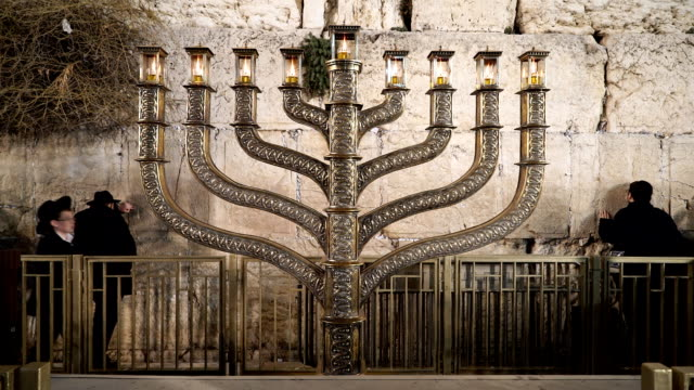 vídeos de stock, filmes e b-roll de menorah oil lamps are illuminated at the wailing wall in the old city. - candelabro