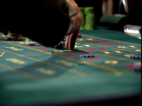 men's and women's hands placing coloured gambling chips on printed green baize casino table - casino stock videos & royalty-free footage