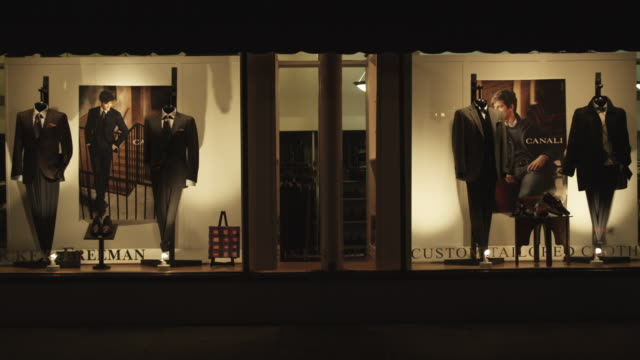 stockvideo's en b-roll-footage met mens' clothes displayed on mannequins in storefront windows. - herenkleding