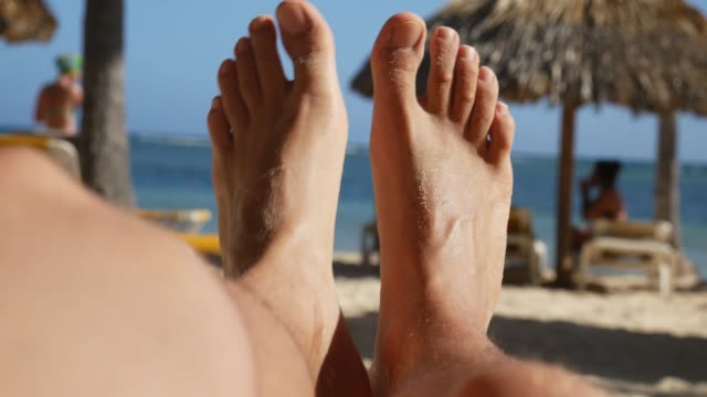 men's feet relaxing on the beach, pov - sunbathing stock videos & royalty-free footage