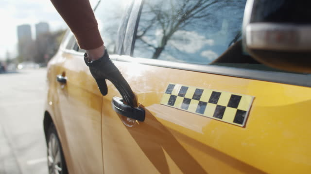 men's hand wearing rubber gloves opening taxi door on a city street during an illness epidemic - yellow taxi video stock e b–roll
