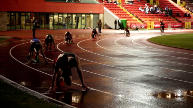 mens student track athletics 1500m race on stadium running track at night with starting pistol no - track and field event stock videos and b-roll footage
