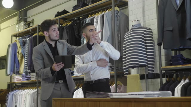 menswear store clerk and customer looking at products on the digital tablet - retail occupation stock videos & royalty-free footage
