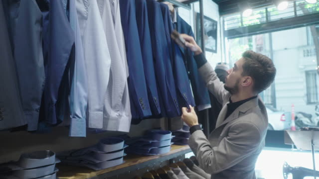 stockvideo's en b-roll-footage met menswear winkel eigenaar borstelen en schoonmaken pakken met wollen borstel - kledingwinkel