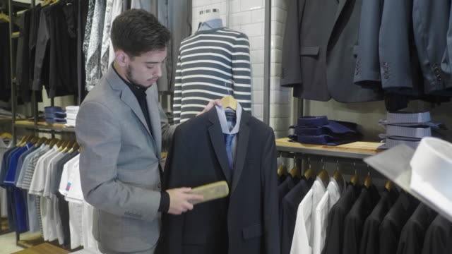 menswear store owner brushing and cleaning suits with wool brush (slow motion) - one young man only stock videos & royalty-free footage