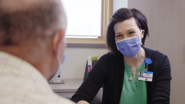 a mental health professional in her forties wearing a face mask talks with a masked white male in his sixties while sitting at a table in a medical clinic - mental illness stock videos & royalty-free footage