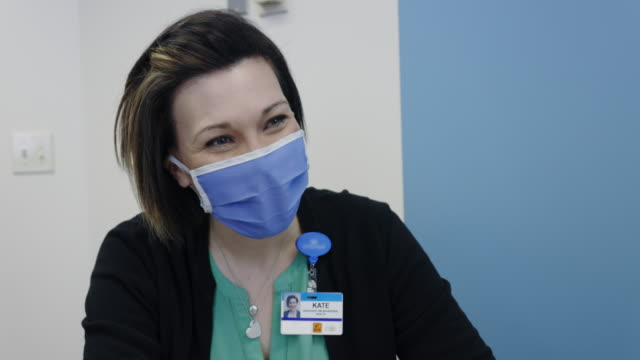 a mental health professional in her forties wearing a face mask talks with a masked white male in his forties while sitting at a table in a medical clinic - resilience stock videos & royalty-free footage