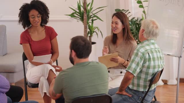 vídeos y material grabado en eventos de stock de profesional de la salud mental hablando con las personas durante la reunión del grupo de apoyo - grupo mediano de personas