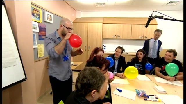 stockvideo's en b-roll-footage met nick clegg visits clock view hospital clegg taking part in exercise to blow up balloons sot / clegg chatting with patients around table sot - geestelijke gezondheidszorg