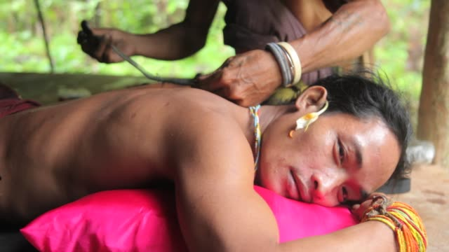 vidéos et rushes de mentawai man getting a traditional tattoo done - culture indigène
